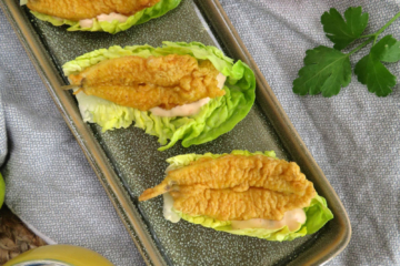 battered fish curry served on a gem lettuce with tartar sauce on the sides
