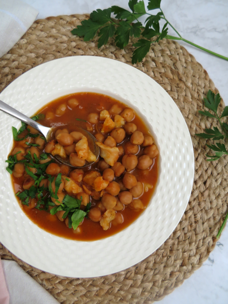 slow cooker chickpea stew with codfish served in a platter -close up view