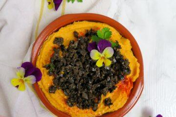 Hummus de zanahoria con olivada y flores comestibles.